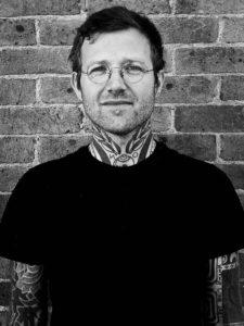 Hand poke tattoo artist Adam Sage standing outside 1770 tattoo studio in Brighton UK