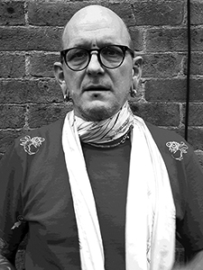 Into You shop owner and tattoo artist Alex Binnie with scarf and glasses on standing outside 1770 tattoo studio in Brighton uk