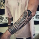 Polynesian inspired half sleeve tattoo on forearm