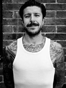 Jack Thomas Newton traditional old school tattoo artist at 1770 in Brighton standing outside the shop in white vest with moustache