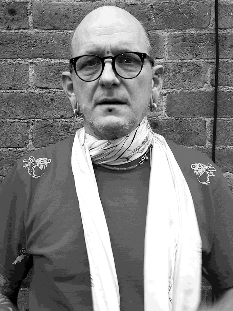 Shop owner and Tattoo artist Alex Binnie with scarf and glasses on standing outside 1770 Tattoo