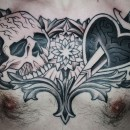 Black and grey chest tattoo with skull on one side and heart and dagger on the other with flower and between them