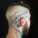 head tattoo of the word revenant in script