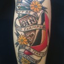 tattoo of bottle of gin and red high heel shoe with three yellows flowers around it and a banner saying if you can't be a good example be a terrible warning