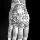 hand tattoo of womans face on top of the hand smoking a cigarette with four dice on the knuckle