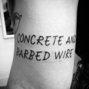 tattoo on back of arm saying concrete and barbed wire