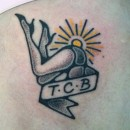 Hand poked tattoo of black and grey ladies legs with banner saying tcb and golden sun