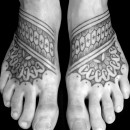 pair of tattooed feet with tribal style pattern and mandalas