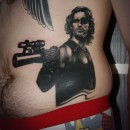 Snake plissken from escape from New York black and grey tattoo on side snake is holding a gun and pointing it at you